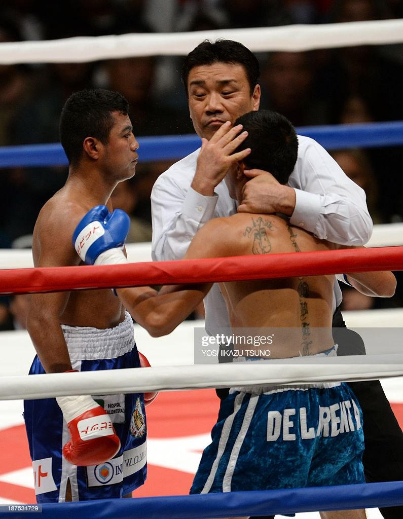 Japanese referee (C) hugs Mexican boxer Oscar Blanquet (R) to stop his boxing match against former WBA lightflyweight champion Nicaraguan Roman Gonzalez (L) in Tokyo on November 10, 2013. Gonzalez defeated Blanquet by TKO in the second round. AFP PHOTO / Yoshikazu TSUNO