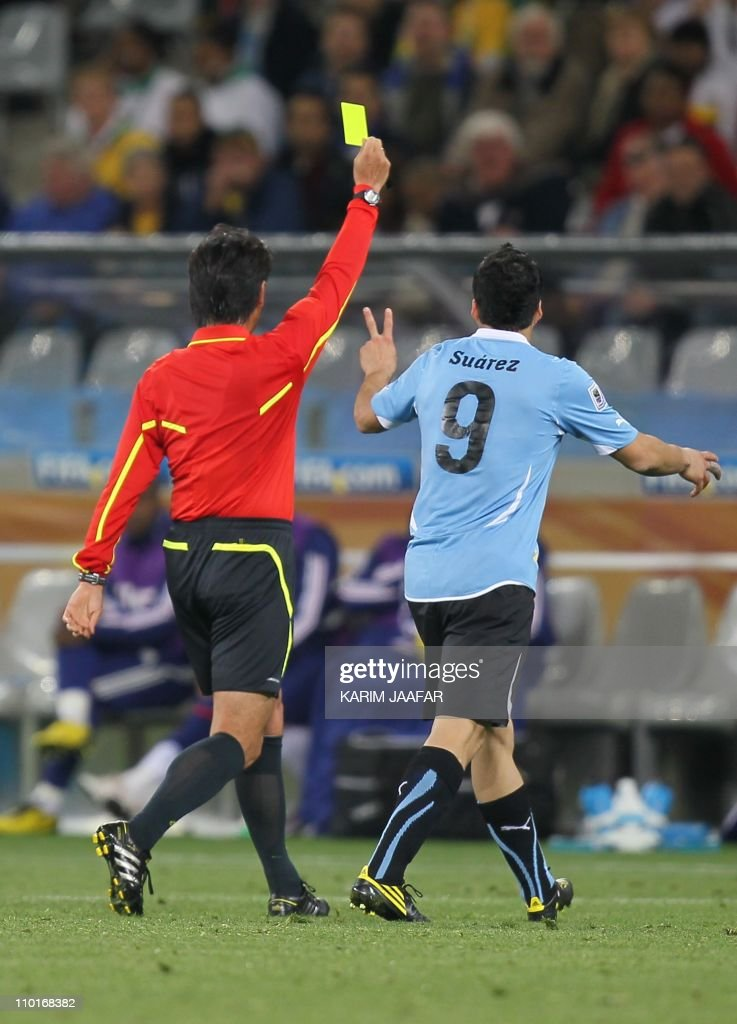 Japanese referee Yuichi Nishimura (L) gives a yellow card to Uruguay's striker Luis Suarez during the Group A first round 2010 World Cup football match Uruguay vs France on June 11, 2010 at Green Point stadium in Cape Town. The match ended in a 0-0 draw. NO