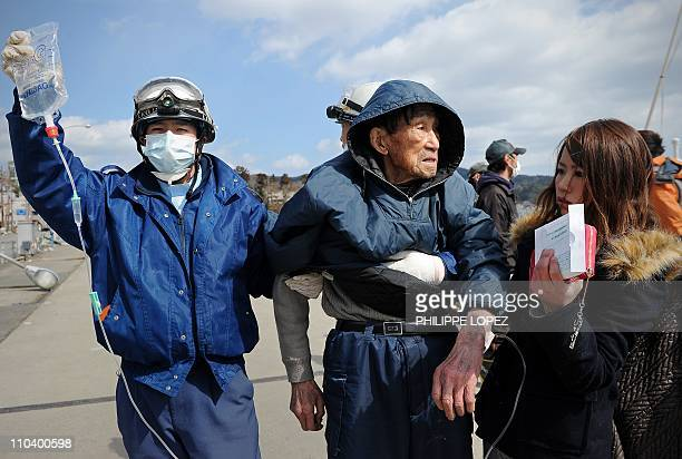 A Japanese rescue worker holds an intravenous drip bag as an elderly survivor is transported to a hospital in Kesennuma in Miyagi prefecture on March...