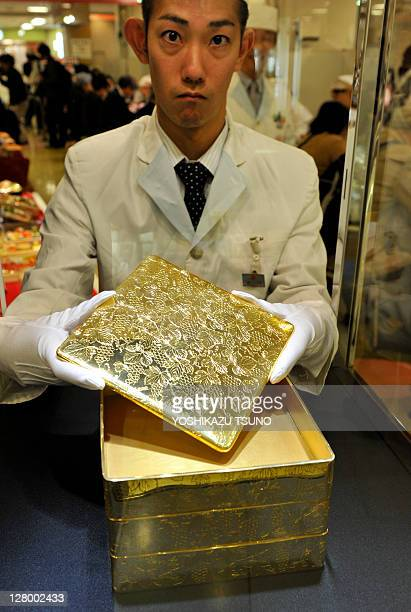 A Japanese restaurant chef displays 18 carat gold 'jubako' boxes used for holding traditional Japanese food during their new year at a department...