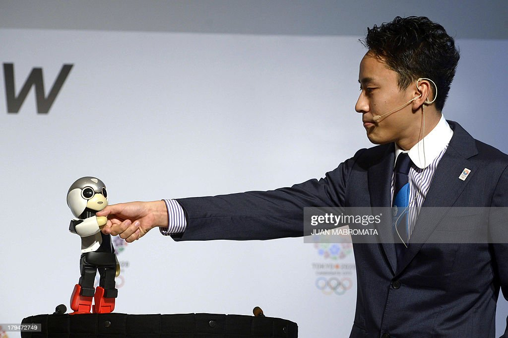 Japanese robot Mirata (L) and Japanese double fencing silver medallist Yuki Ota shake hands during a news conference given by IOC member and President of Japanese Olympic Committee and Tokyo 2020 Tsunekazu Takeda, on September 4, 2013 in Buenos Aires, Argentina, where the International Olympic Committee will elect the host city of the 2020 Summer Olympic Games on September 7 also will consider adding a new sport for the 2020 Olympic program and elect a new president on September 10.