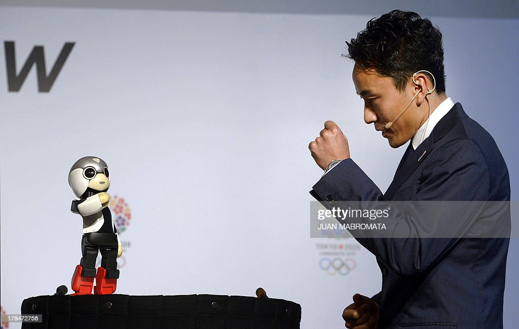 Japanese robot Mirata (L) and Japanese double fencing silver medallist Yuki Ota perform during a news conference given by IOC member and President of Japanese Olympic Committee and Tokyo 2020 Tsunekazu Takeda, on September 4, 2013 in Buenos Aires, Argentina, where the International Olympic Committee will elect the host city of the 2020 Summer Olympic Games on September 7 also will consider adding a new sport for the 2020 Olympic program and elect a new president on September 10. AFP PHOTO /JUAN MABROMATA