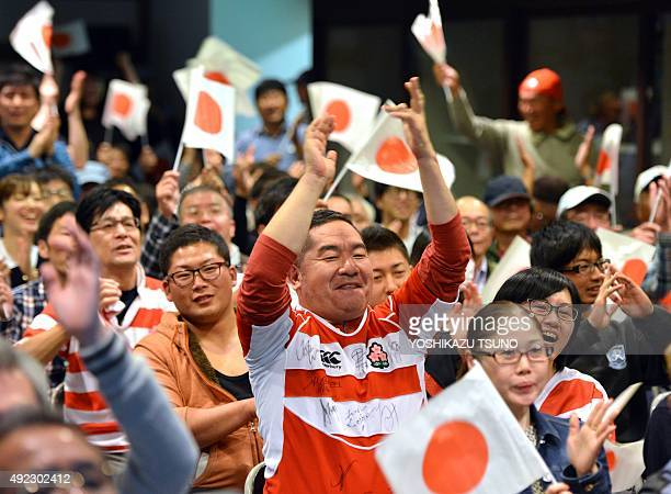 Japanese rugby fans celebrate their team's try during a public viewing of the Rugby World Cup match against the United States in Kumagaya in Saitama...