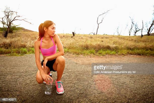 Japanese runner crouching on road