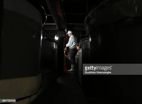 Japanese sake brewery worker stirs fermenting sake at Tanaka Sake Brewery on January 24 2014 in Himeji Japan Japanese Prime Minister Shinzo Abe...