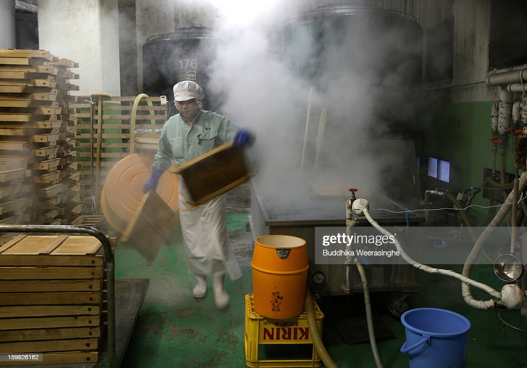 Japanese sake brewery worker wahses steam rice store containers at Tatsuriki sake brewery on January 21, 2013 in Himeji, Japan. The Hyogo prefecture is the largest sake producing region in Japan.