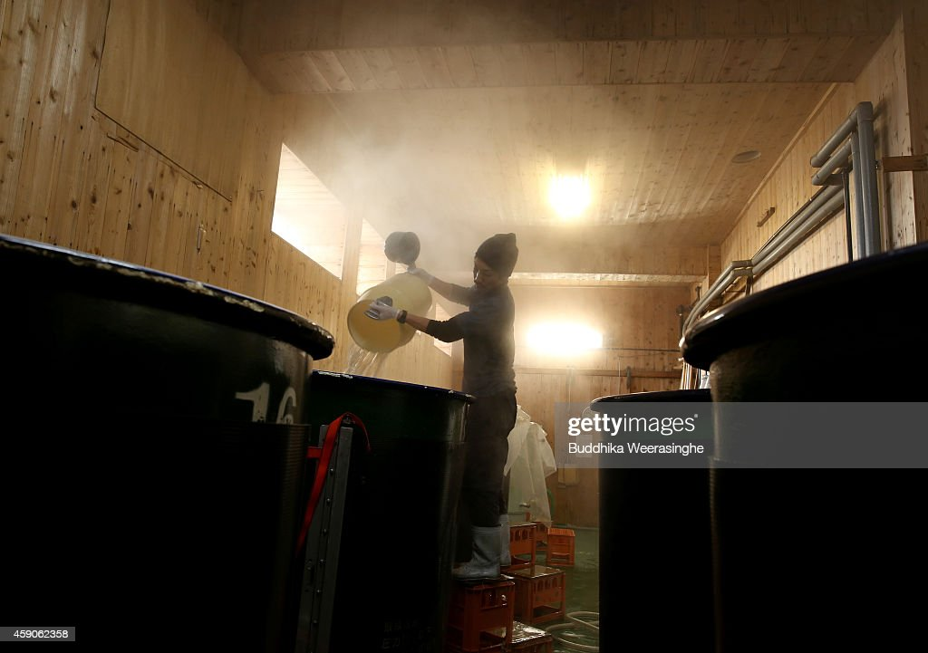 Japanese sake brewery worker washes sake tanks as preparation for brewing sake during the first day of sake production at NadagikuShozo sake brewery...