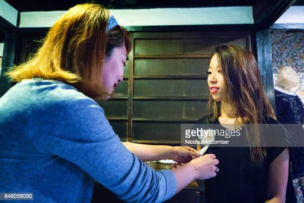 Japanese saleswoman places floral accessory on female customer