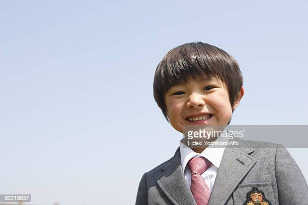 Japanese schoolboy smiling against clear sky