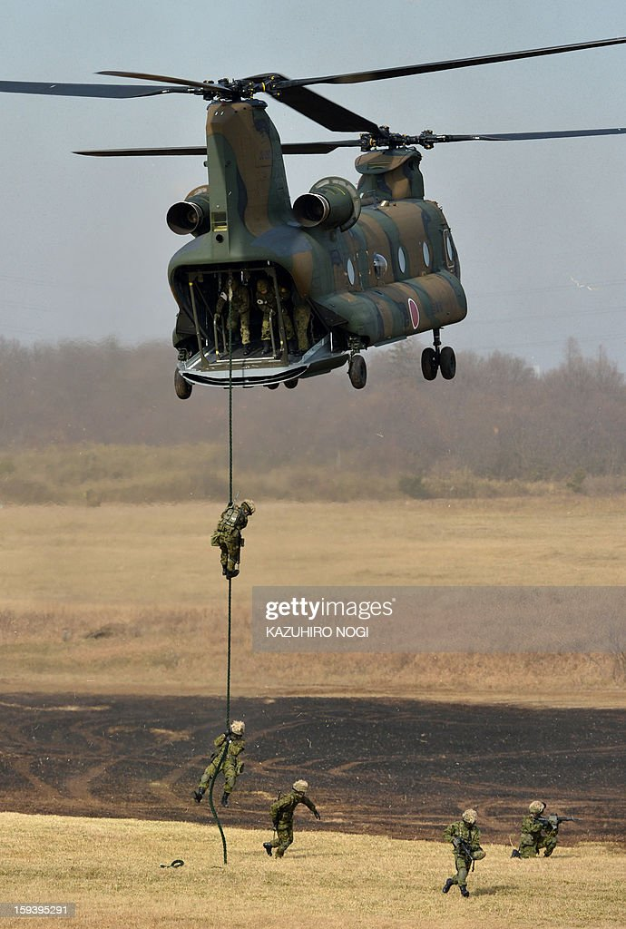 Japanese Self Defense Force ground troops participate in a new year military drill with a helicopter at the training grounds in Narashino, suburban Tokyo on January 13, 2013. A total of 300 personnel, 20 aircraft and 33 vehicles took part in the open exercise at the defense force's Narashino training ground.
