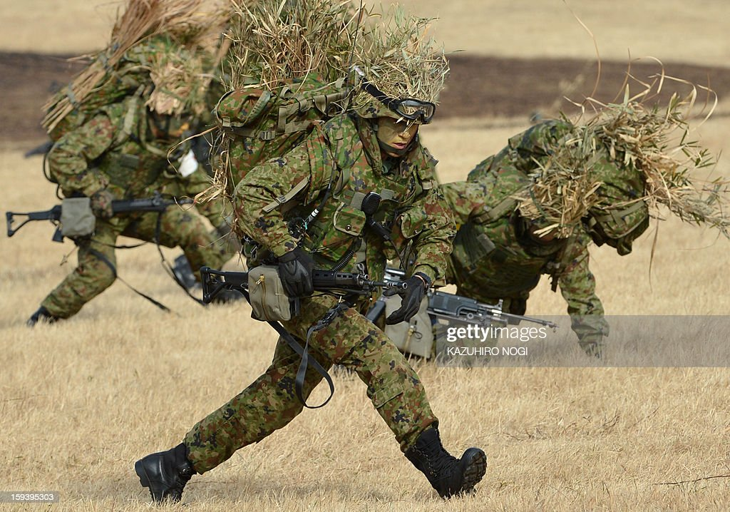 Japanese Self Defense Force ground troops participate in a new year military drill at the training grounds in Narashino, suburban Tokyo on January 13, 2013. A total of 300 personnel, 20 aircraft and 33 vehicles took part in the open exercise at the defense force's Narashino training ground. AFP PHOTO / KAZUHIRO NOGI