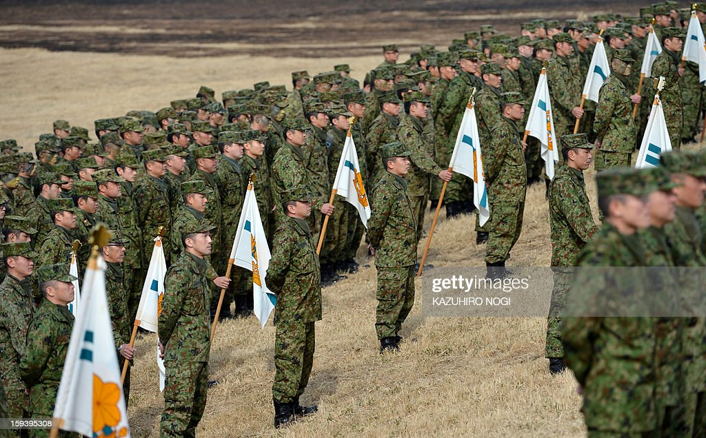 Japanese Self Defense Force ground troops participate in a new year military drill at the training grounds in Narashino, suburban Tokyo on January 13, 2013. A total of 300 personnel, 20 aircraft and 33 vehicles took part in the open exercise at the defense force's Narashino training ground.