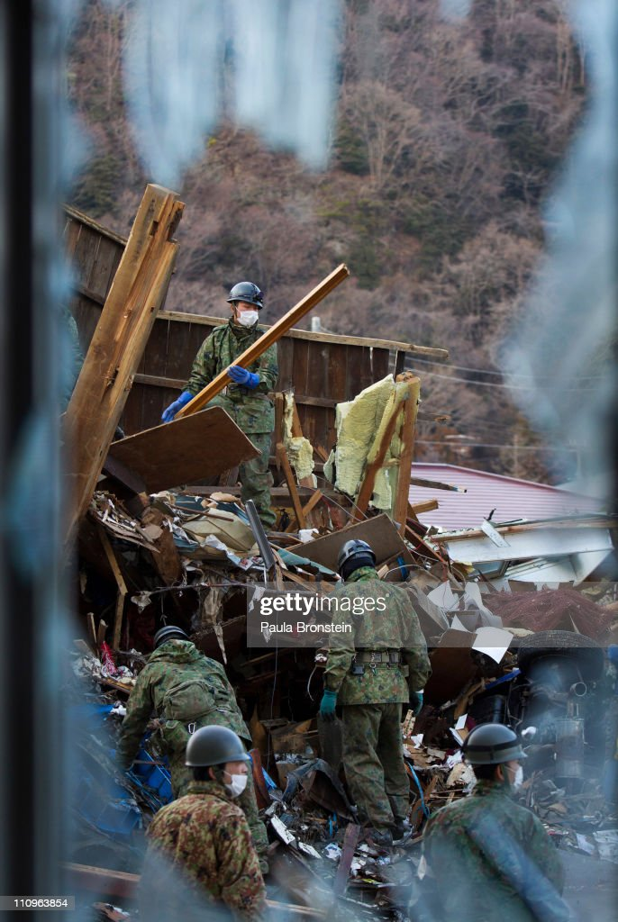 ISHINOMAKI, JAPAN - MARCH 28 Japanese Self Defense Force members clear debris looking for bodies in the rubble March 28, 2011 in Ishinomaki, Miyagi, Japan. Thousands of earthquake victims are packed into various evacuation centers causing health problems for the elderly and some children living in tight quarters with no privacy. More than two weeks after the magnitude 9 earthquake and tsunami struck Japan, the death toll has risen to over 11,000 dead with thousands missing, and the expectation is that it may end up well over 20,000. Presently the country is still struggling to repair a damaged nuclear power plant that could soon be leaking highly contaminated water into the ocean.