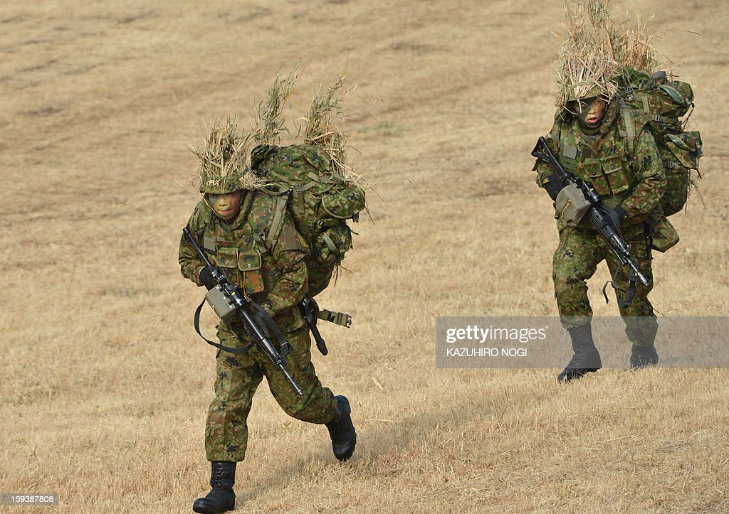 Japanese Self Defense Force troops participate in a new year military drill at the training grounds in Narashino, suburban Tokyo on January 13, 2013. A total of 300 personnel, 20 aircraft and 33 vehicles took part in the open exercise at the defense force's Narashino training ground.
