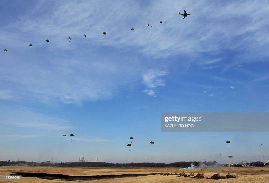 Japanese Self Defense Forces ground troops parachute into the air from a military transport aircraft during a new year drill in Narashino, suburban Tokyo on January 13, 2013. A total of 300 personnel, 20 aircraft and 33 vehicles took part in the open exercise at the defense force's Narashino training ground. AFP PHOTO / KAZUHIRO NOGI