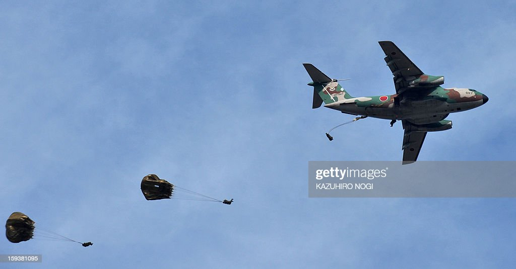 Japanese Self Defense Forces ground troops parachute into the air from a military transport aircraft during a new year drill in Narashino, suburban Tokyo on January 13, 2013. A total of 300 personnel, 20 aircraft and 33 vehicles took part in the open exercise at the defense force's Narashino training ground.