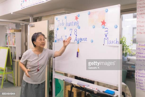 語学学校でスピーチを与える日本の年配の女性