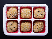 Japanese sesame mochi (sticky rice cakes) in plastic tray isolated on black background