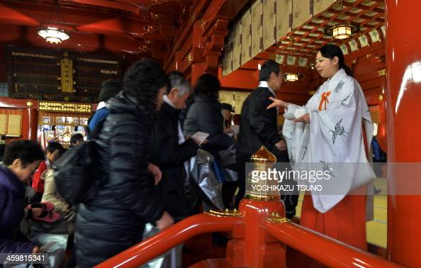 A Japanese Shinto maiden greets worshippers as they enter the Kanda shrine to celebrate the New Year in Tokyo on January 1 2014 Million of Japanese...