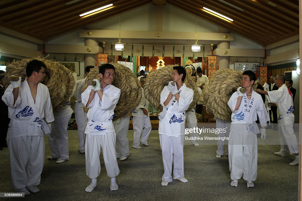 Japanese Shinto shrine priests carry the Shimenawa, Sacred ropes for hang to between God Married Stones during the Oshimenawahari ceremony of Meoto-iwa or the Couple Rock at Futami Okitama Shrine on May 5, 2016 in Ise, Japan. The Oshimenawahari ceremony is held three times a year to exchange the 35 meters long heavy rope made of rice straw that connects the sacred Couple Rock - one small, one big. The Couple Rock serves as a gate to the Okitama Shrine, dedicated to the god Sarutahiko and goddess Ukanomitama from Japanese myth.