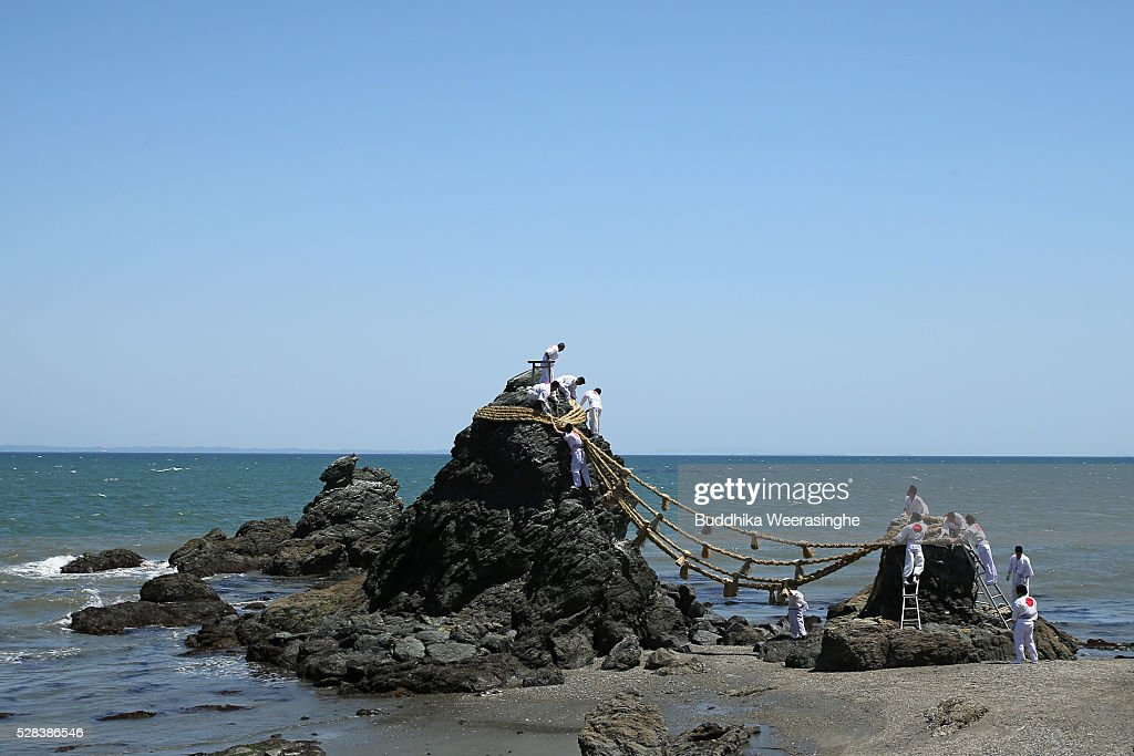 Japanese Shinto shrine priests hang the shimenawa, or the sacred ropes, between the Meotoiwa, or the sacred Couple Rock during the Oshimenawahari ceremony at Futami Okitama Shrine on May 5, 2016 in Ise, Japan. The Oshimenawahari ceremony is held three times a year to exchange the 35 meters long heavy rope made of rice straw that connects the sacred Couple Rock - one small, one big. The Couple Rock serves as a gate to the Okitama Shrine, dedicated to the god Sarutahiko and goddess Ukanomitama from Japanese myth.