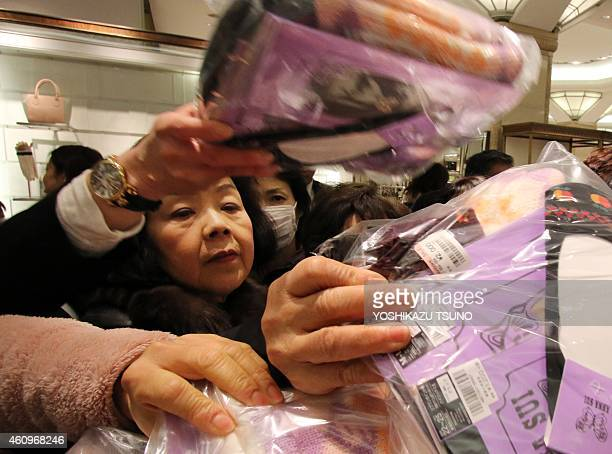 Japanese shoppers pick up 'lucky bags' containing items worth three times their price tag during a department store sale to celebrate a new year of...
