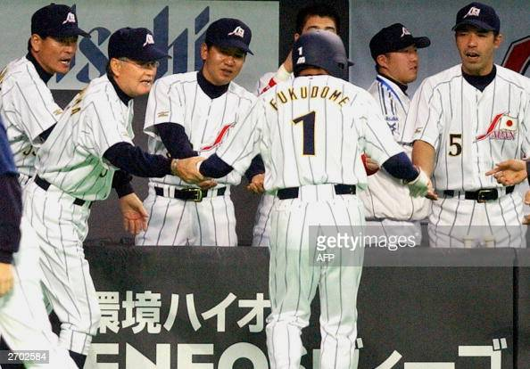Japanese slugger Kousuke Fudome is welcomed by his teammates and manager Shigeo Nagashima during the Asian Baseball Championships against Taiwan at...
