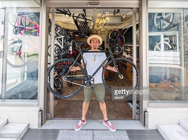 Japanische kleine Geschäftsmann hält ein Fahrrad vor seinem Fahrrad Shop