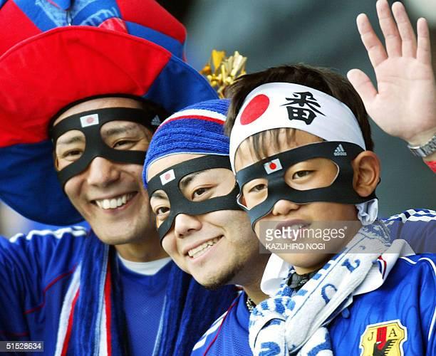 Japanese soccer fans wear protective masks like Japan's defender Naoki Matsuda as they cheer at Miyagi Stadium Japan 18 June 2002 before match 55...
