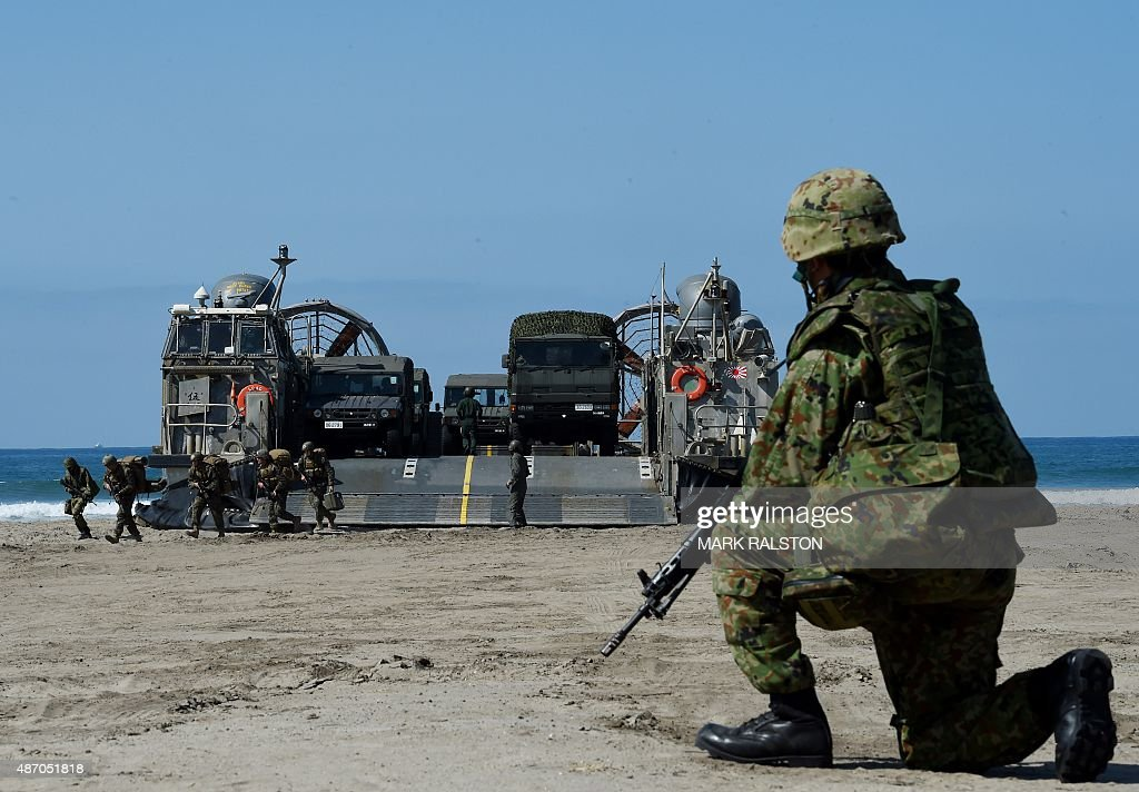 A Japanese soldier keeps watch over a Japanese Landing Craft Air Cushion hovercraft during an amphibious landing operation with US Forces and the...