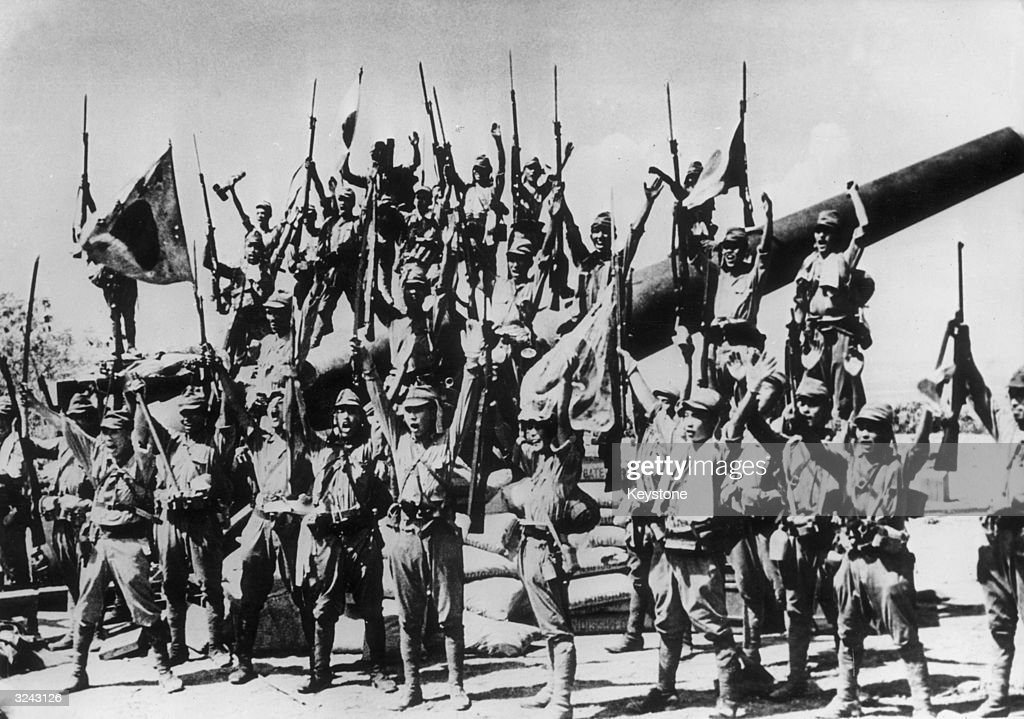Japanese soldiers celebrate after capturing an American gun emplacement in the Bataan province of the Philippines
