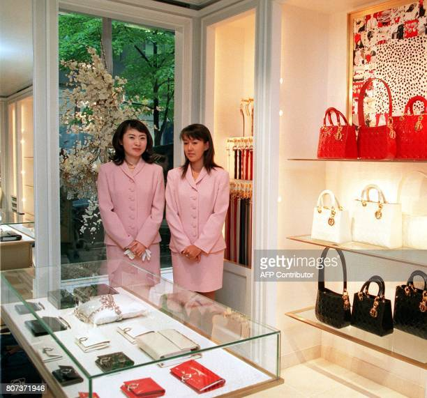 Japanese staff of newly opened French boutique Christian Dior pose behind a showcase at the opening ceremony in Ginza central Tokyo 06 April The...