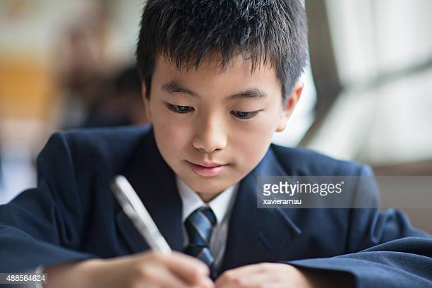 Japanese student boy working at his classroom desk