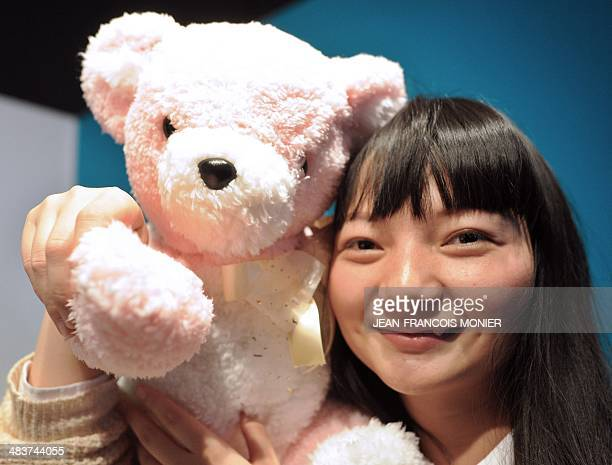 Japanese student Li Yuanyan from the Hasegawa Lab holds a teddy bear robot with sensors capable to display its 'mood' on April 9 at the 16th edition...