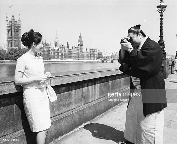 Japanese sumo wrestler Taiho Kaki taking a picture of his wife Yoshiko next to the Houses of Parliament London June 12th 1967