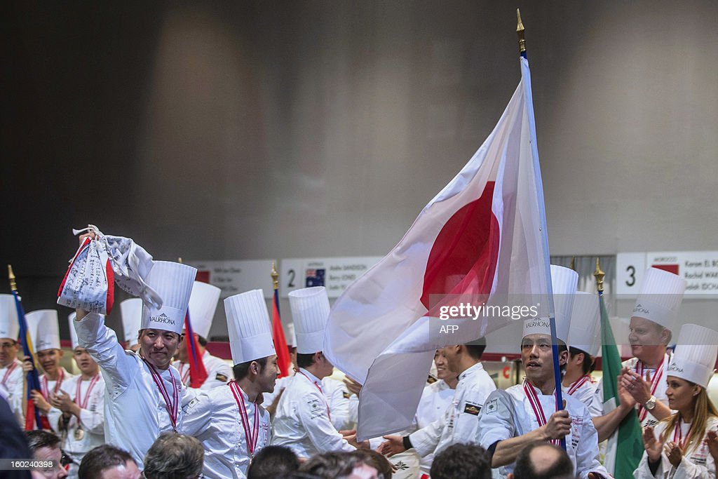 Japanese team headed by Tetsuro Akasaki (R waving the Japanese national flag) celebrates as other contenders applaud after finishing second of the final of the World Cup of pastries, on January 28, 2013 during the catering and food international show (SIRHA), in the French central town of Chassieu, near Lyon.
