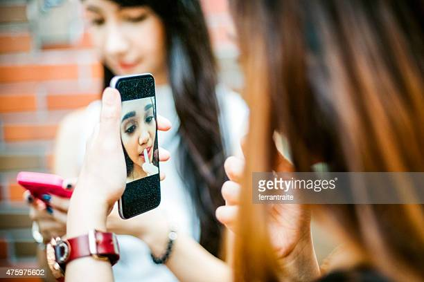 Japanese Teenage Girls using Smartphone as Vanity Mirror