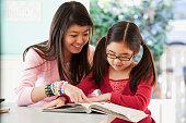 Japanese teenager helping sister with homework