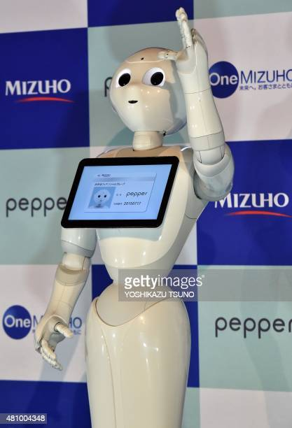Japanese telecom giant Softbank's humanoid robot Pepper receives the staff identity card of Japan's Mizuho Bank during a ceremony for new bank...