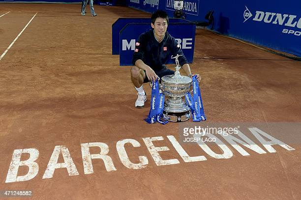 Japanese tennis player Kei Nishikori poses with his trophy as he celebrates his victory over Spanish tennis player Pablo Andujar after the final of...