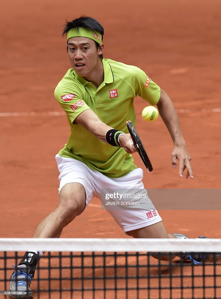 Japanese tennis player Kei Nishikori returns a ball to French tennis player Richard Gasquet during the Madrid Open tournament at the Caja Magica (Magic Box) sports complex in Madrid on May 5, 2016. / AFP / JAVIER