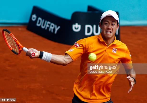 Japanese tennis player Kei Nishikori returns the ball to Spanish player David Ferrer during the ATP Madrid Open in Madrid on May 11 2017 / AFP PHOTO...