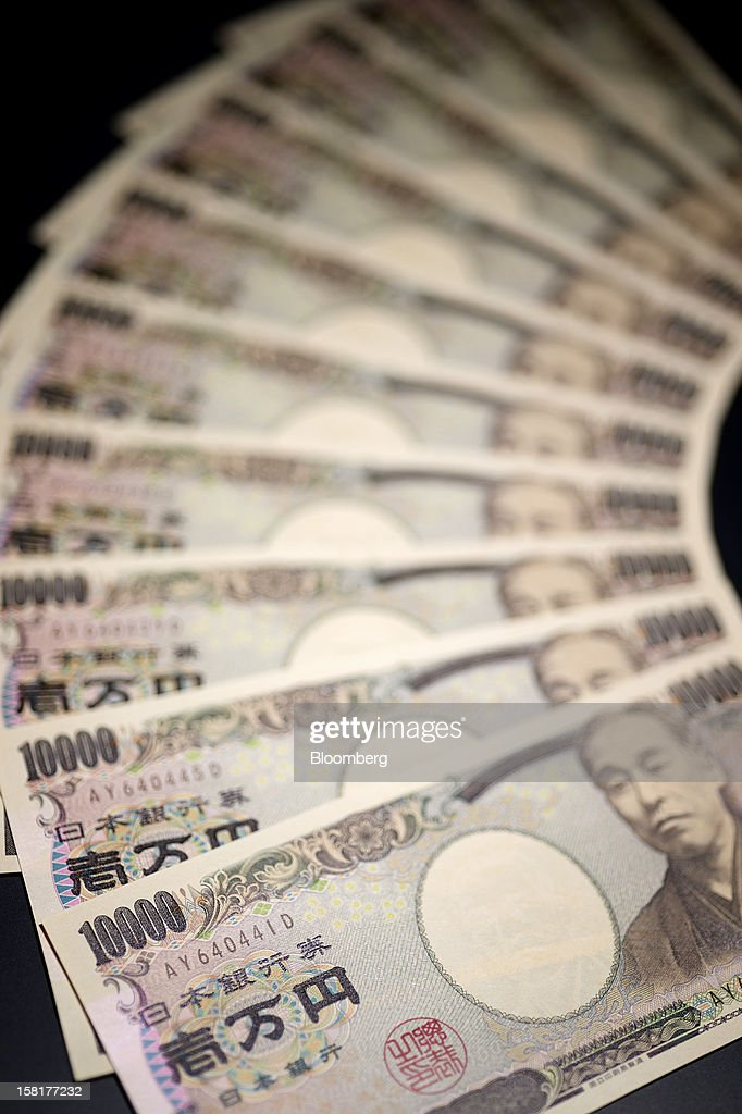 Japanese ten-thousand yen banknotes are arranged for a photograph in Kawasaki, Kanagawa Prefecture, Japan, on Monday, Dec. 10, 2012. The yen is losing its status as a haven for risk-averse investors as Japan lurches toward a chronic trade deficit and the front-runner to become the next prime minister calls for unlimited central-bank stimulus. Photographer: Akio Kon/Bloomberg via Getty Images