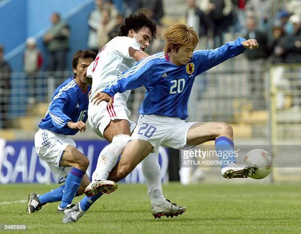 Japanese Toshiya Fujita teammate Kejiti Tamada vies with Hungarian midfielder Peter Lipcsei in Zalaegerszeg 25 April 2004 during a friendly football...
