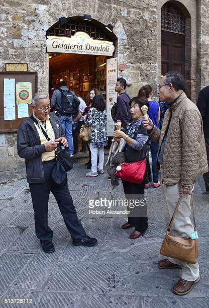 Japanese tourists enjoy cones of gelato or Italian ice cream from the Gelateria di Piazza also known as Gelateria Dondoli in the medieval walled hill...