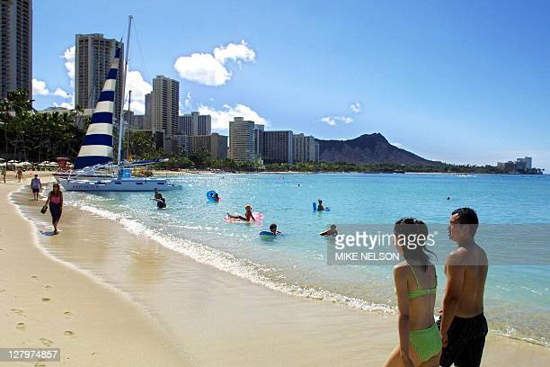 Japanese tourists stroll along Waikiki Beach in Hawaii 06 September following a shark siting 05 September which closed the world famous beach until...