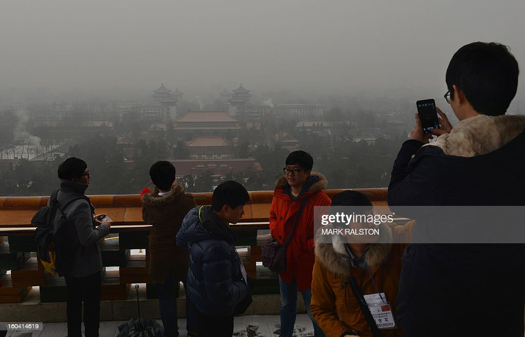 Japanese tourists take photos from the historic Jingshan Park as smog continues to shroud Beijing on January 31, 2013. Doctors in Beijing said on January 31 that hospital admissions for respiratory complaints rose in recent days during the latest bout of air pollution to cover northern China. AFP PHOTO/Mark RALSTON