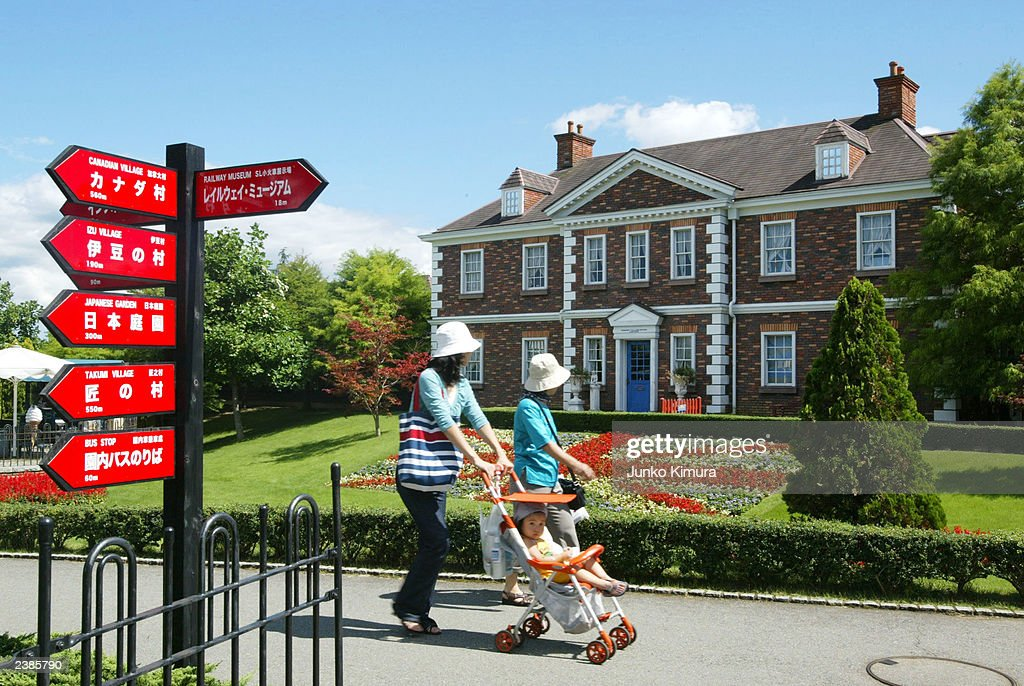 Japanese Tourists Walk By English Styled Buildings At An English Village Theme  Park On August