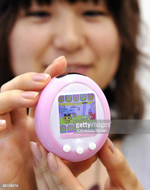 Japanese toy giant Bandai employee displays the new virtual pet toy with 152inch color LCD display 'Tamagotchi plus color' megahit eggshaped portable...