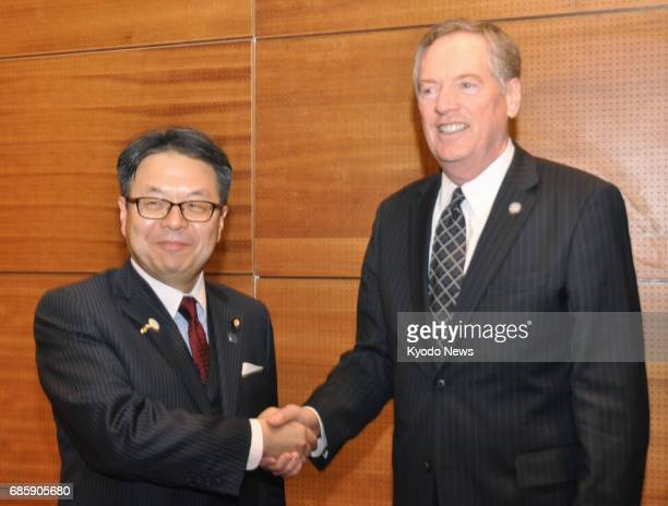 Japanese trade minister Hiroshige Seko and Robert Lighthizer the new US trade representative shake hands in Hanoi Vietnam on May 20 2017 They agreed...